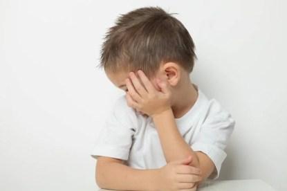 Bambino si copre viso con una mano