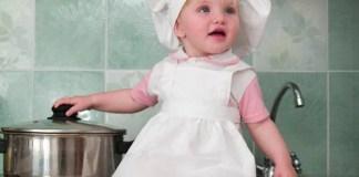 Bambina con cappello da chef vicino a pentola
