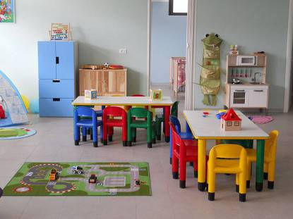 La stanza di un asilo nido, con piccoli tavoli e sedioline colorate