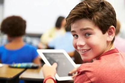 Un bambino sta usando un tablet in classe (registro elettronico)
