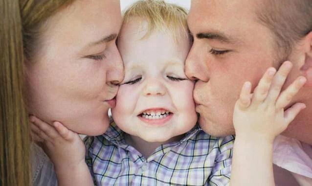 papa e mamma baciano loro bambino