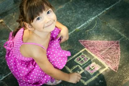 Little Girl Drawing on the sidewalk