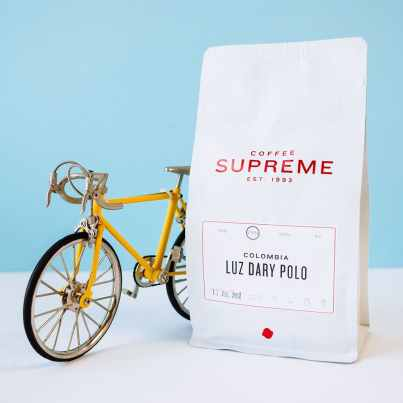 Coffee Supreme Colombia Luz Dary Polo coffee with toy yellow bicycle
