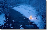 Illuminated Christmas tree beside a creek in a snow covered forest at dusk, Cascade Mountains, Washington, USA
