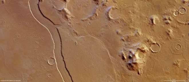 Una vista de color natural de Reull Vallis. Se cree que el canal similar al río se formó por el flujo del agua, que en una época distante cortó el terreno de las tierras altas y sucesivamente formó llanuras lisas. Con un ancho de cerca de 7 km y una profundidad de alrededor de 300 m, el suelo del valle muestra características lineales claras que se cree son ricas en hielo y formadas por escombros y hielo de una manera no muy diferente a la formación de valles glaciales en la Tierra.