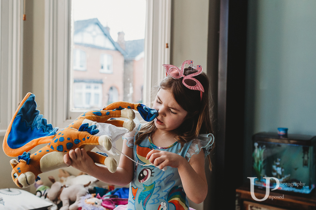 Young girl trying to work out why a soft toy is not working.