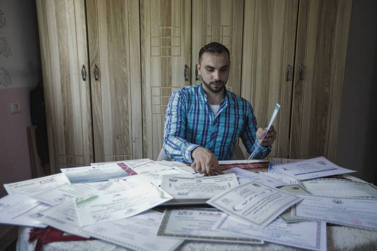 26-year-old Yasser Al-Saied, Palestine refugee with his training, volunteering and graduation certificates at his home in Bureij camp, central Gaza Strip © 2018 UNRWA Photo by Khaled Tuiema.