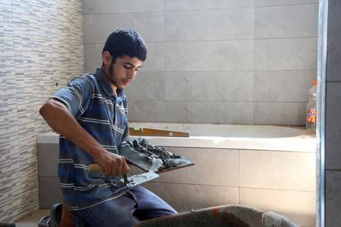 Palestine refugee Abed Al-Rahim during his work in tiling. © 2018 UNRWA Photo by Khalil Adwan