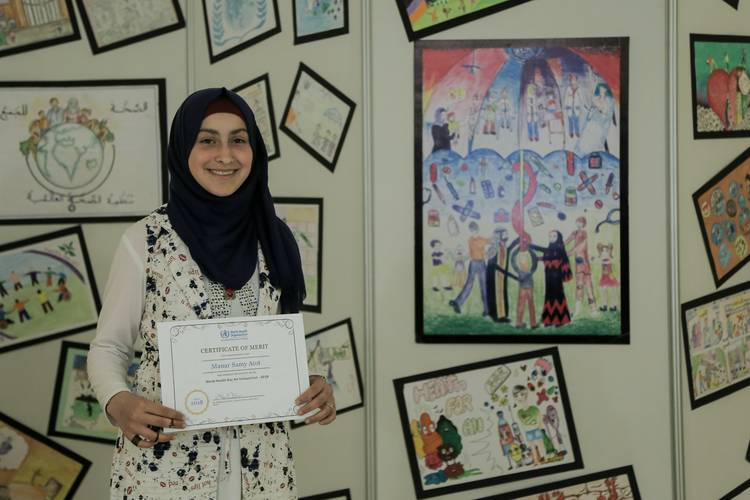 Manar Sami Atot, a 14-year-old UNRWA student, holding her certificate of merit next to her winning artwork at the final ceremony of the WHO art competition held on 10 April at Rashad Al Shawwa centre, Gaza city. © 2018 UNRWA Photo by Khaled Tuaima