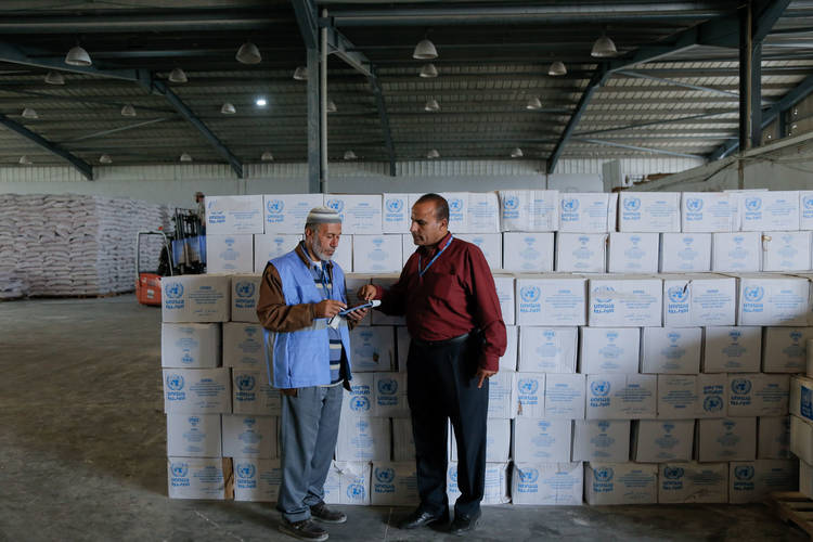 Mr. Jamal Al-Buri, UNRWA Storekeeper (left), and his supervisor Mr. Naser Mukhimer, check quantities in one of the 17 warehouses UNRWA runs in the Karni Warehousing Industrial Zone in the northern Gaza Strip. © 2017 UNRWA Photo by Tamer Hamam