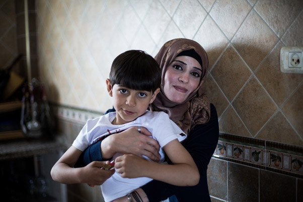 Thirty-six-year-old Heyam Farahat holding her son, 6-year-old Ali, in their home in Rafah, southern Gaza. © 2016 UNRWA Photo by Tamer Hamam