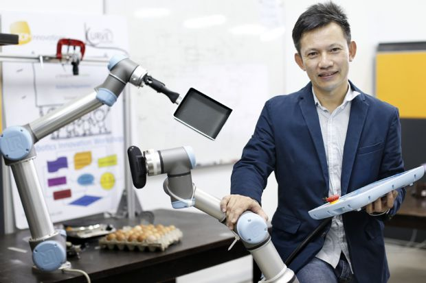 """Even if the initial idea sounds amazing, it is important to network and develop the idea."" - Hui Wing Feh, director, Kurve Automation, seen here with a robot he programmed to make omelettes. (Image from Business Times)"