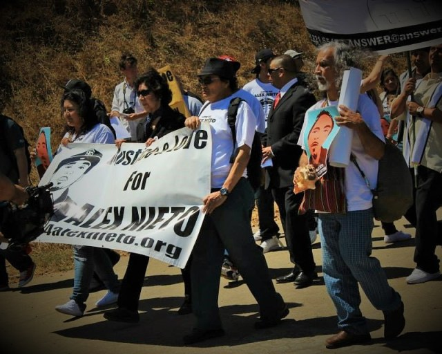 "September 2014, Elvira and Refugio Nieto alongside supporters start marching from Bernal to the Federal Court carrying a banner showing Alex Nieto's image by Oree Originol from the ""Justice for Our Lives"" series exhibited at Take This Hammer exhibit."