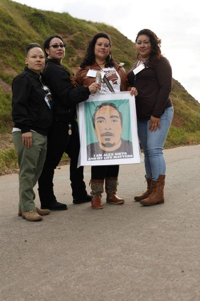 "Photo Credit: Nina Parks, 2014. Homegirls, friends of Alex, holding silkscreened posters ""I am Alex Nieto and my life matters"" by Jesus Barraza of Dignidad Rebelde collective."