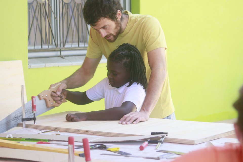 Fransesco helping a young girl to saw wood
