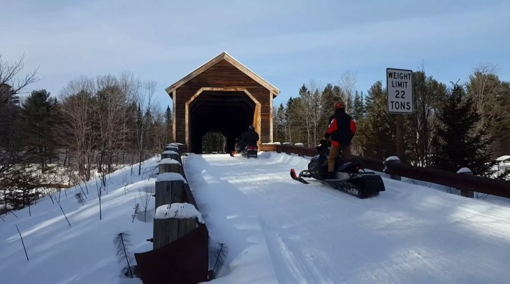 Snowmobiling through Low's Covered Bridge on ITS 85 in Maine