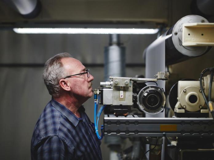 Ein Mitarbeiter überwacht die Produktion einer Beschichtungsrolle: Das Unternehmen ist in den Spartne grafische Medien, Bruchschutz und Industriebeschichtung aktiv. © Neschen Coating GmbH