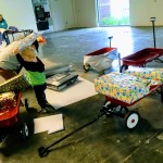 Little boy playing with the gifts while his dad is wrapping gifts at the Family Giving Tree warehouse.