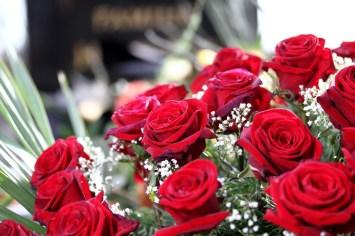 Rote Rosen vor einem Grabstein