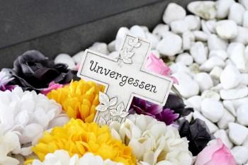 Weißes Kruzifix mit Unvergessen Schriftzug in einem Trauergesteck
