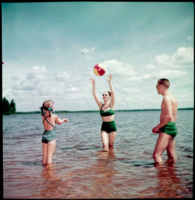 Man, woman and young girl playing with a beach ball in the water at the beach (circa 1950). Canada. National Film Board of Canada. Photothèque. Library and Archives Canada, e010955762 CC by 2.0