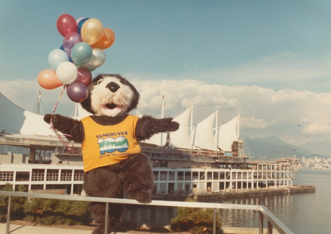 "Erickson, Glen E., ""Tillicum posing with balloons in front of Canada Place (1986),"" City of Vancouver Archives, Vancouver Centennial Commission fonds AM1576-S6-12-F45-: 2011-010.2719"