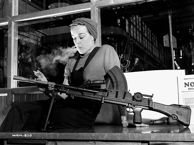 "Veronica Foster, an employee of the John Inglis Co. Ltd. Bren gun plant, known as ""The Bren Gun Girl"" poses with a finished Bren gun at the John Inglis Co. plant. May 1941. National Film Board of Canada. Photothèque / Library and Archives Canada / e000760403."