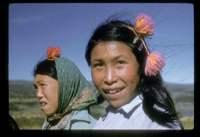 Two Inuit girls standing together out side.