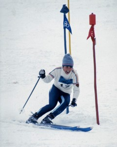 This image shows a woman competing in an Olympic downhill ski competition. She is on the slopes, having just gone through two slalom gates. She is wearing a blue and white uniform, and a fiercely competitive look on her face.