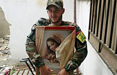 A Hezbollah fighter respectfully picks up an image of the Mother of God from the ruins of a church destroyed by US-backed Takfiris