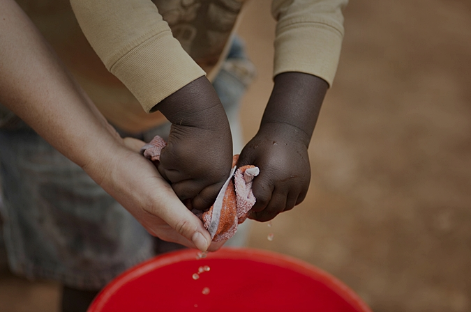 Adult is helping african child with washing cloth
