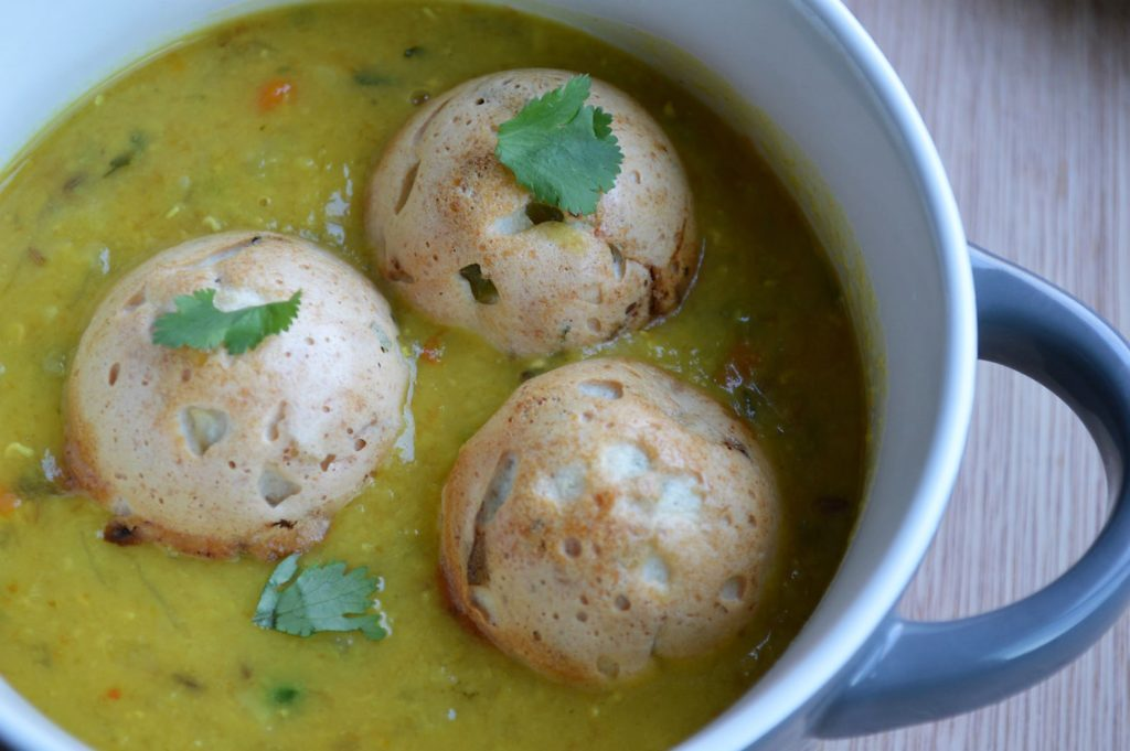 Baked bonda soup recipe using baked urad dal. Bondas spiced with south indian flavors floating in a warm, nourishing light soup. A protein packed meal or snack that can be made vegan by replacing the butter | upgrademyfood.com