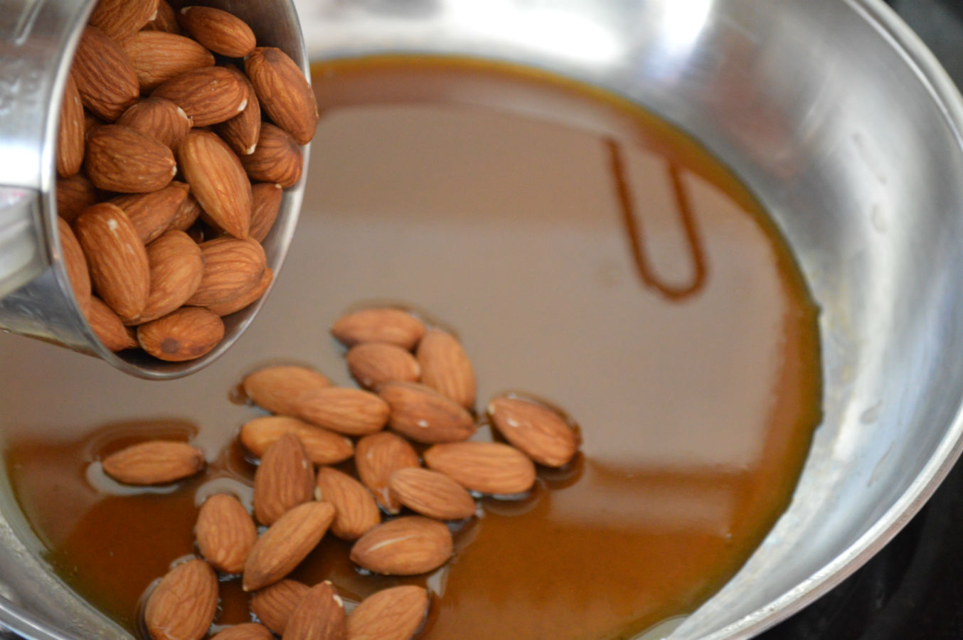 Add almonds to jaggery syrup