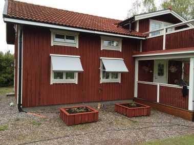 Fönstermarkis Java monterad på falurött hus