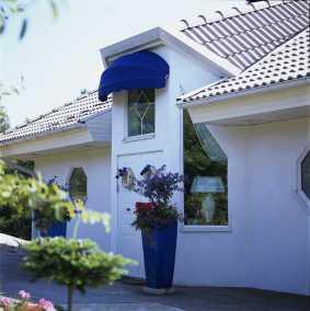 Korgmarkis Sienna blå monterad på vitt modernt hus