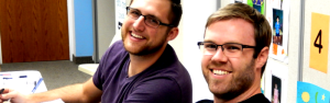 two guys smiling.