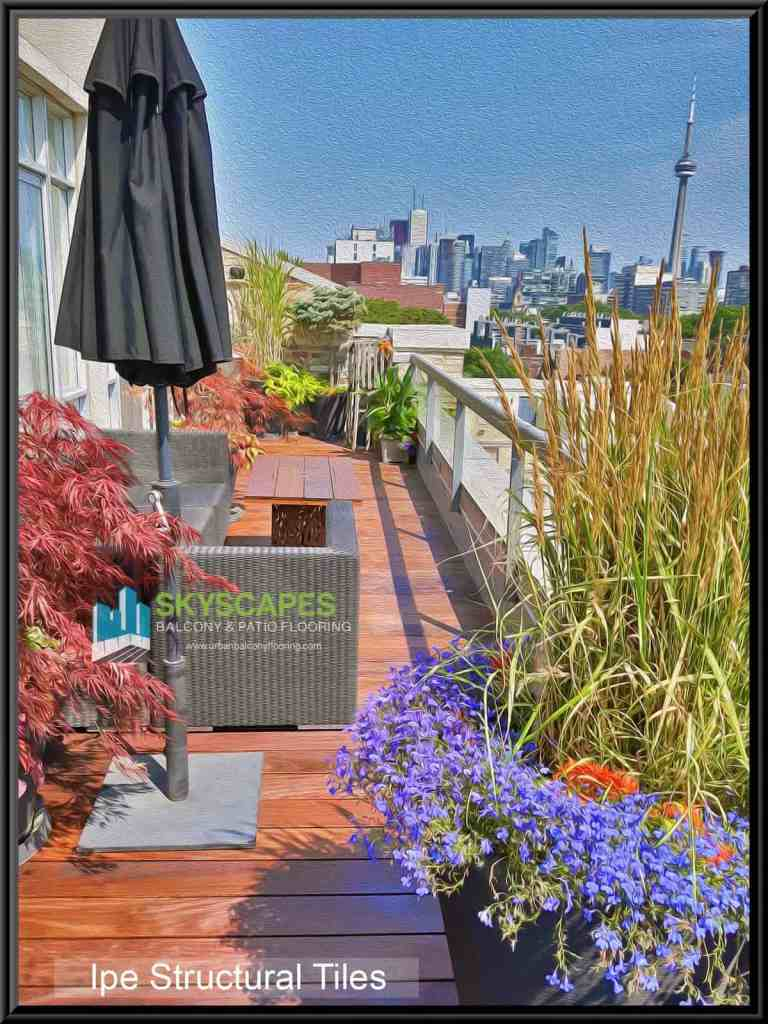 Beautiful flowers with Ipe Structural wooden outdoor flooring on Toronto terrace showing CN tower in background. Skyscapes logo in mid-left of image. Digitally enhanced oil-paint strokes using Adobe Photoshop.