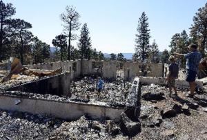 0715 NWS SquibbFire2-js.jpg Mark Squibb, far right, and his children Dakota, 11, left, Tanner, 6, center, and Hunter, 8, look over the remains of their home that was destroyed in the High Park fire.