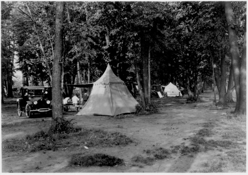 a couple of tents, and some cars among the trees in a campground