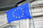 Le drapeau européen flotte au vent sur un fond d'architecture