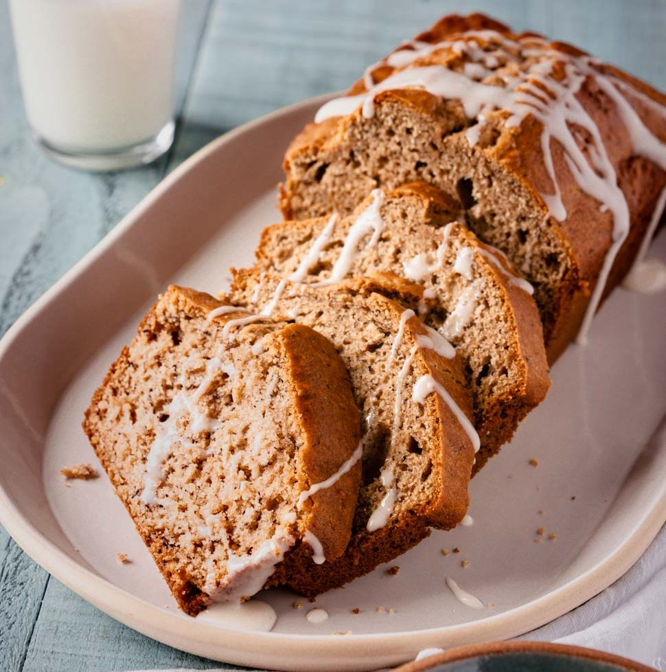 Banana bread loaf with slices drizzled with glaze