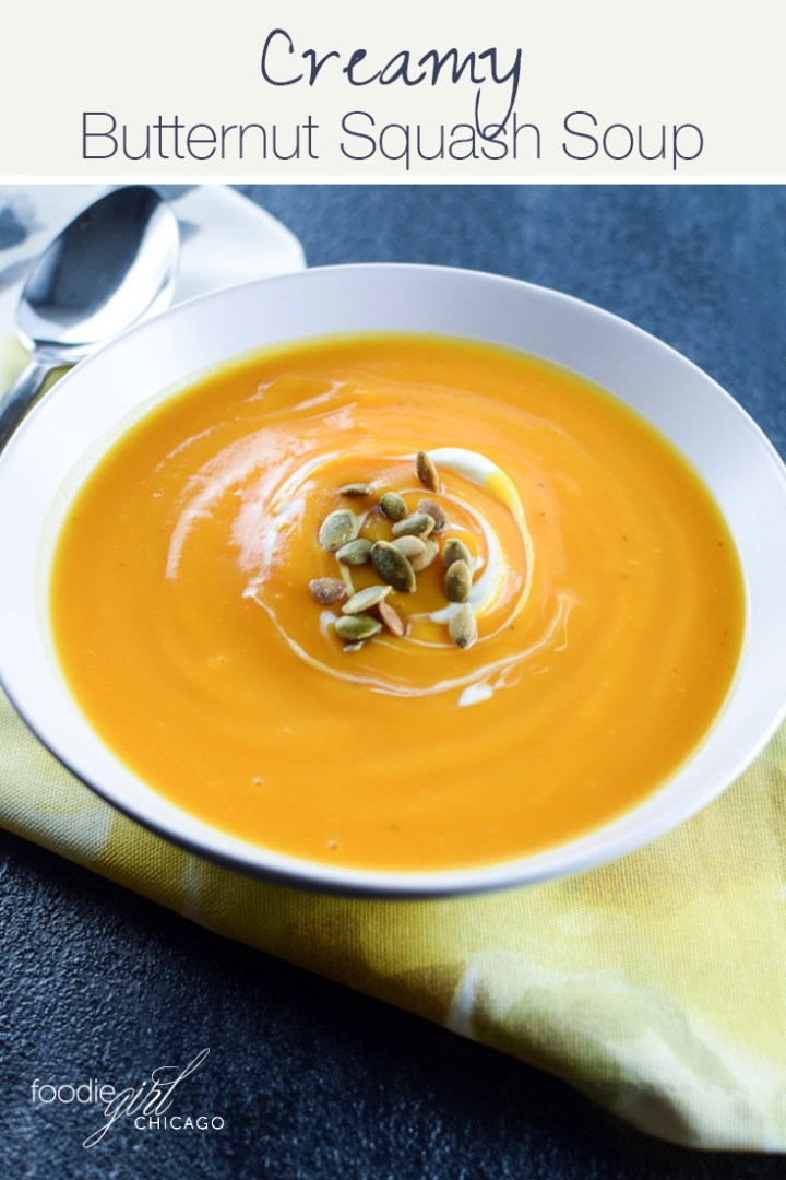 Creamy butternut squash soup with a swirl of creme fraiche and a sprinkle of pepitas