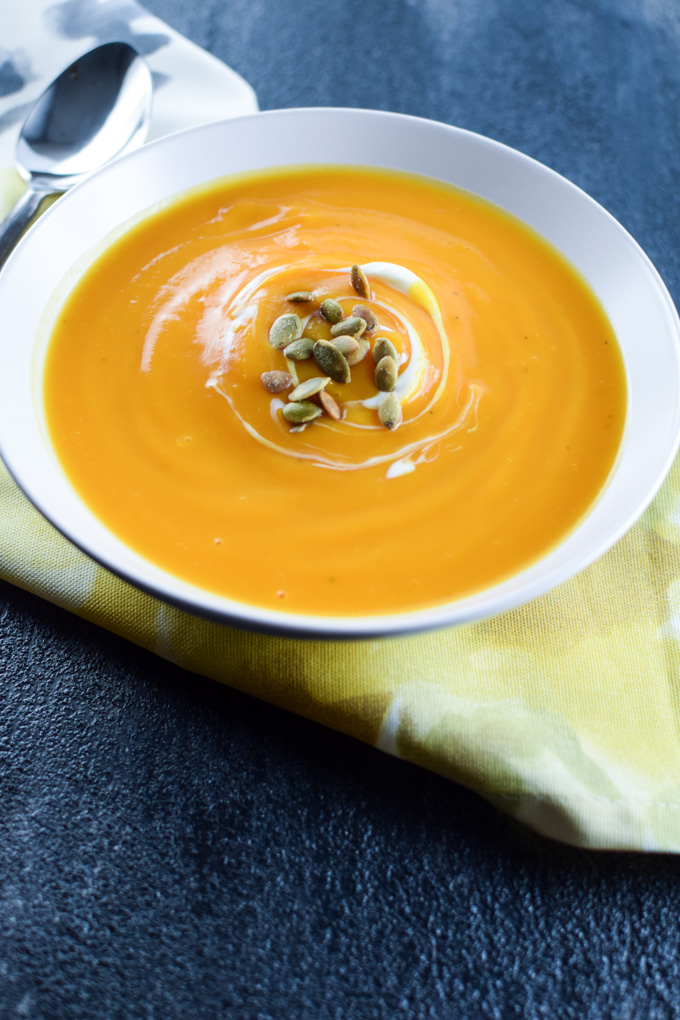 Creamy Butternut Squash Soup in cream bowl topped with toasted pepita seeds