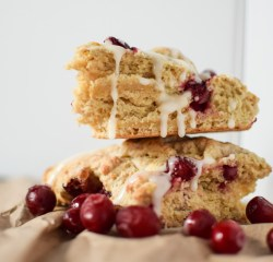 Two glazed Orange Cranberry Scones stacked and drizzled with glaze