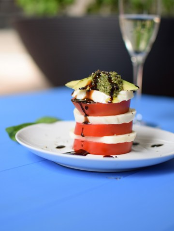 Tomato and fresh mozzarella slices stacked on a white plate, topped with basil pesto and drizzled with balsamic glaze