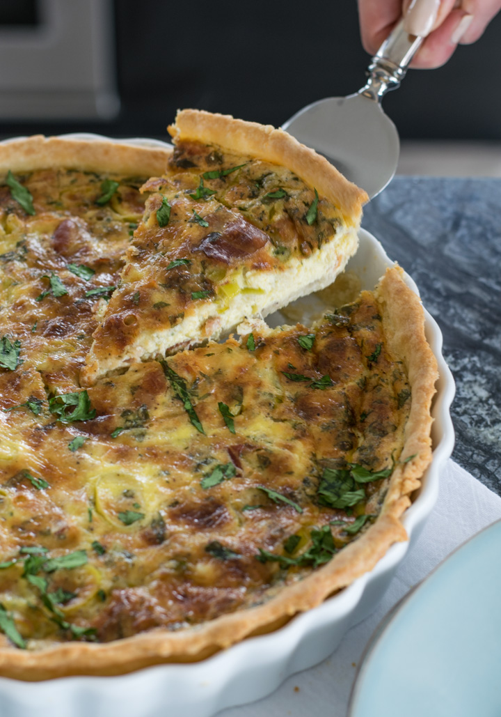 A slice of Leek & Pancetta Quiche being lifted from the quiche pan