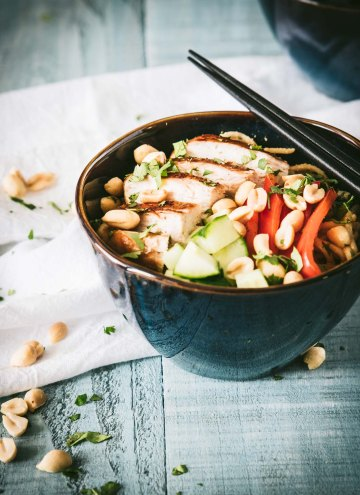 Udon noodles topped with grilled chicken, peanut sauce and veggies