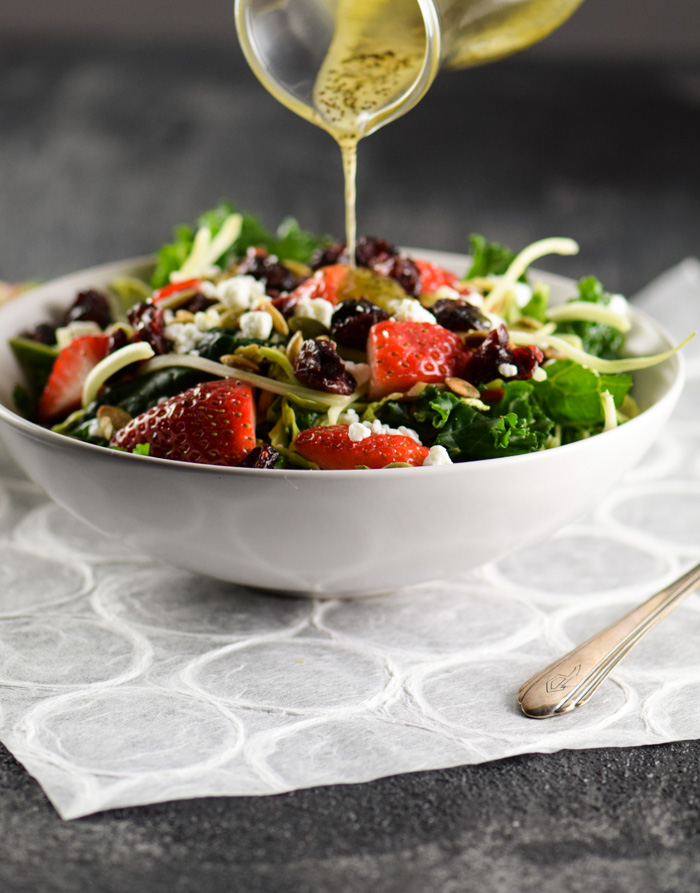 Poppy seed dressing being poured over Strawberry, Brussels Sprouts Kale Salad