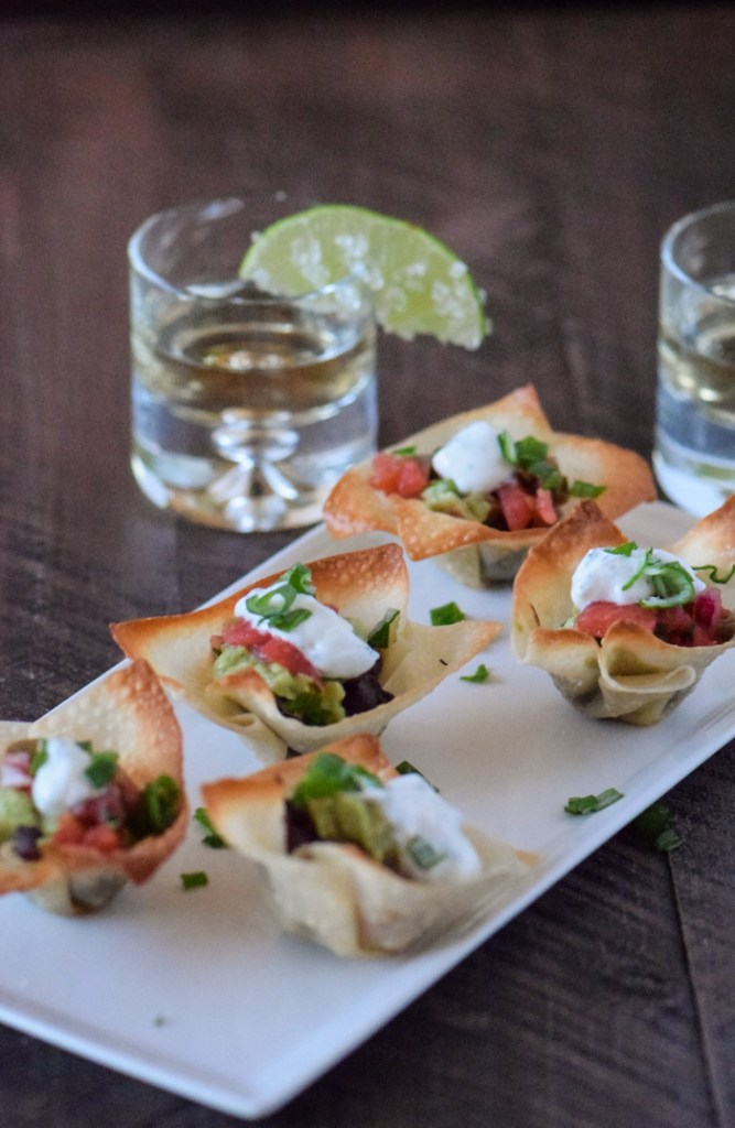 Five wonton cups filled with black beans, salsa, guacamole and greek yogurt