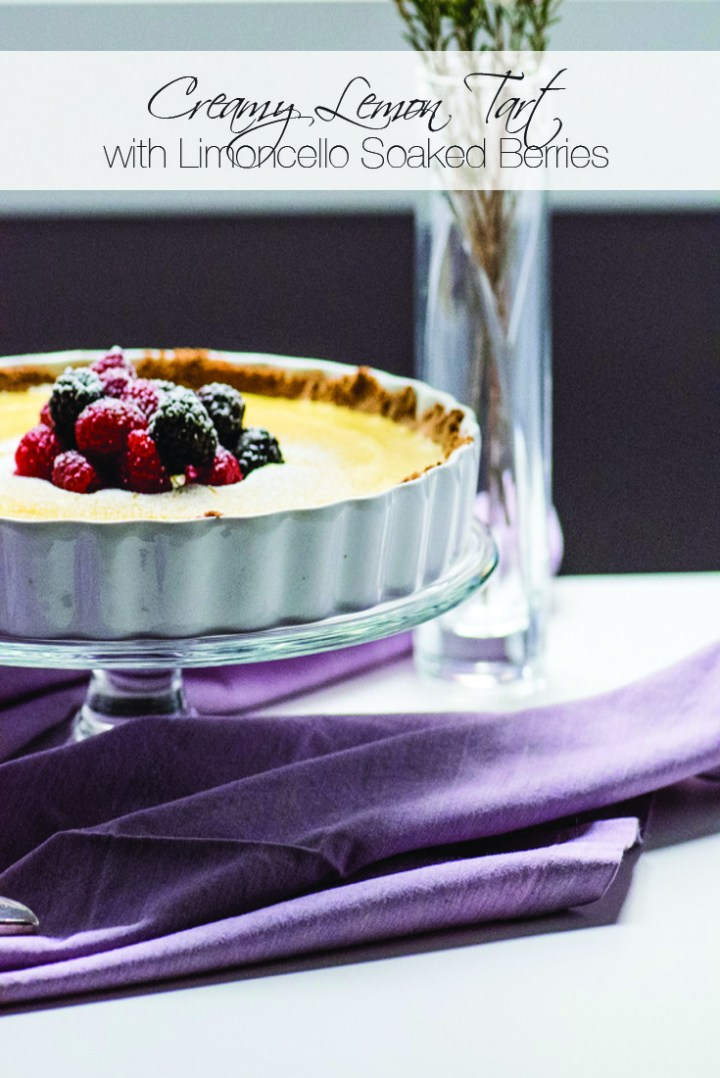 Creamy lemon tart topped with berries on a glass cake stand